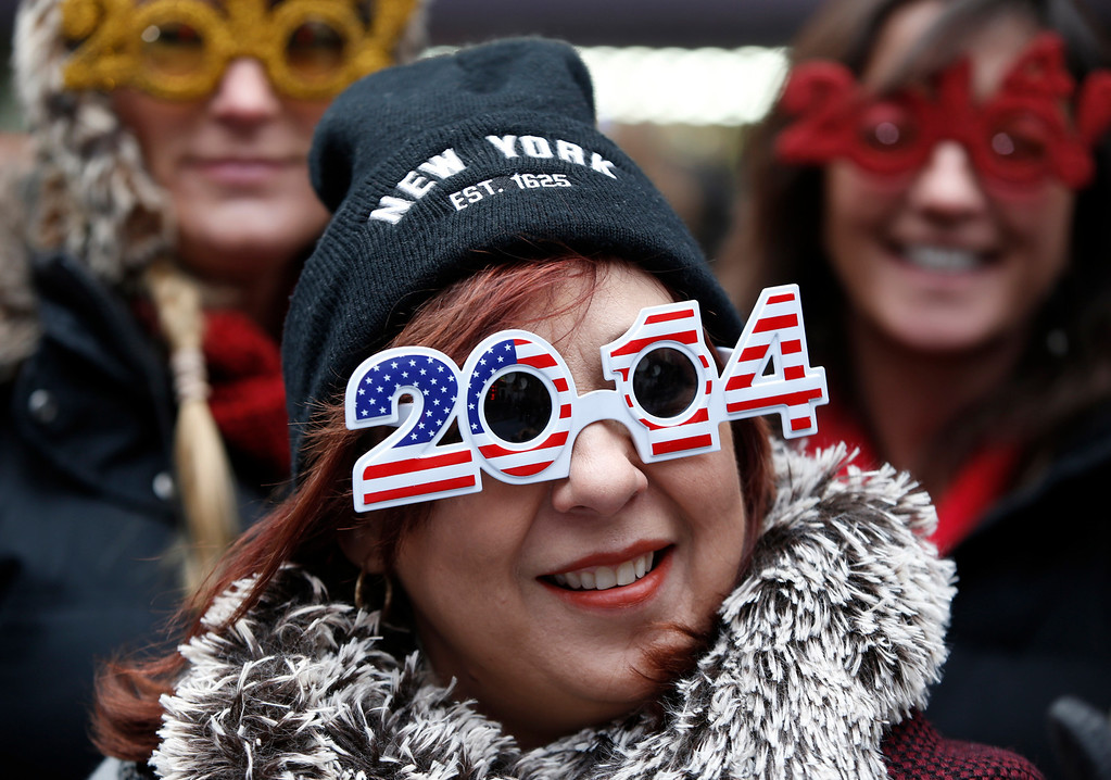 . Carmen Glavan, of Monterrey, Mexico, wears 2014 glasses with an American theme as she and others wait in Times Square for the midnight ball drop on New Year\'s Eve, Tuesday, Dec. 31, 2013, in New York. The crowds will have to wait more than ten hours for the ball drop. (AP Photo/Kathy Willens)