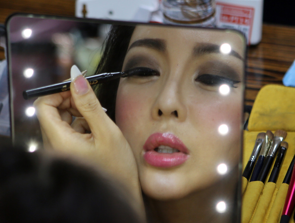 . Arisa of South Korea applies makeup on her eye during a backstage photo session at the Miss International Queen 2013 transgender beauty pageant in Pattaya, southeastern Thailand Friday, Nov. 1, 2013. Twenty-five contestants from 17 countries participate in this year\'s pageant which has been held for nine respective years. (AP Photo/Apichart Weerawong)