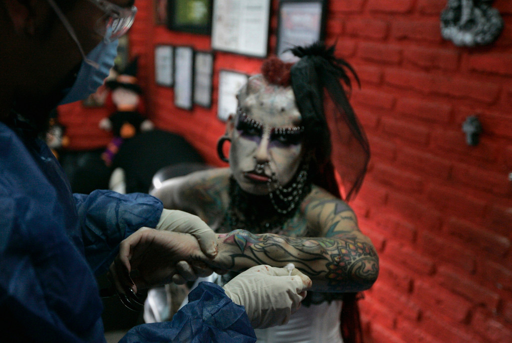 ". Maria Jose Cristerna, 36, a mother of four, a tattoo artist and a former lawyer, sits in her tattoo parlor and boutique after getting 3D body implants inserted in her lower arm in Guadalajara February 4, 2012. Cristerna, who is dubbed ""Vampire Woman\"" but prefers to be identified as \""Jaguar Woman\"", had her first tattoo when she was 14 and decided to physically transform herself after having gone through 10 years of domestic violence in her first marriage. Women in Mexico celebrate International Women\'s Day on March 8. Picture taken February 4, 2012  REUTERS/Alejandro Acosta"