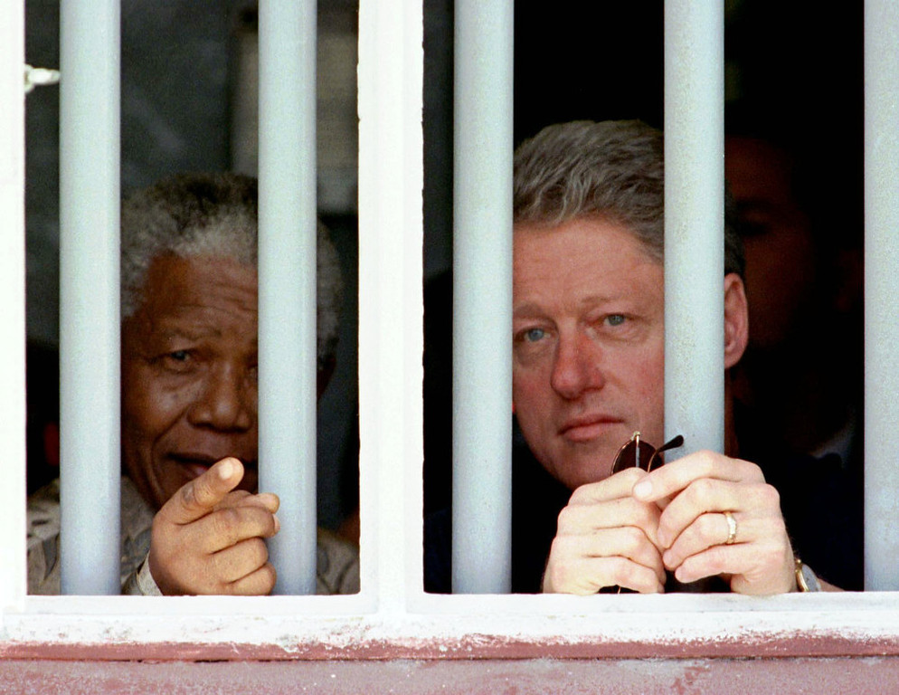 . In this March 27, 1998 file photo, President Clinton and South African President Nelson Mandela  peer through the bars of prison cell No. 5, the cramped, gray cell where Mandela was jailed for 18 years in his struggle  against apartheid on Robben Island, South Africa.  (AP Photo/Rick Wilking/Pool, file)