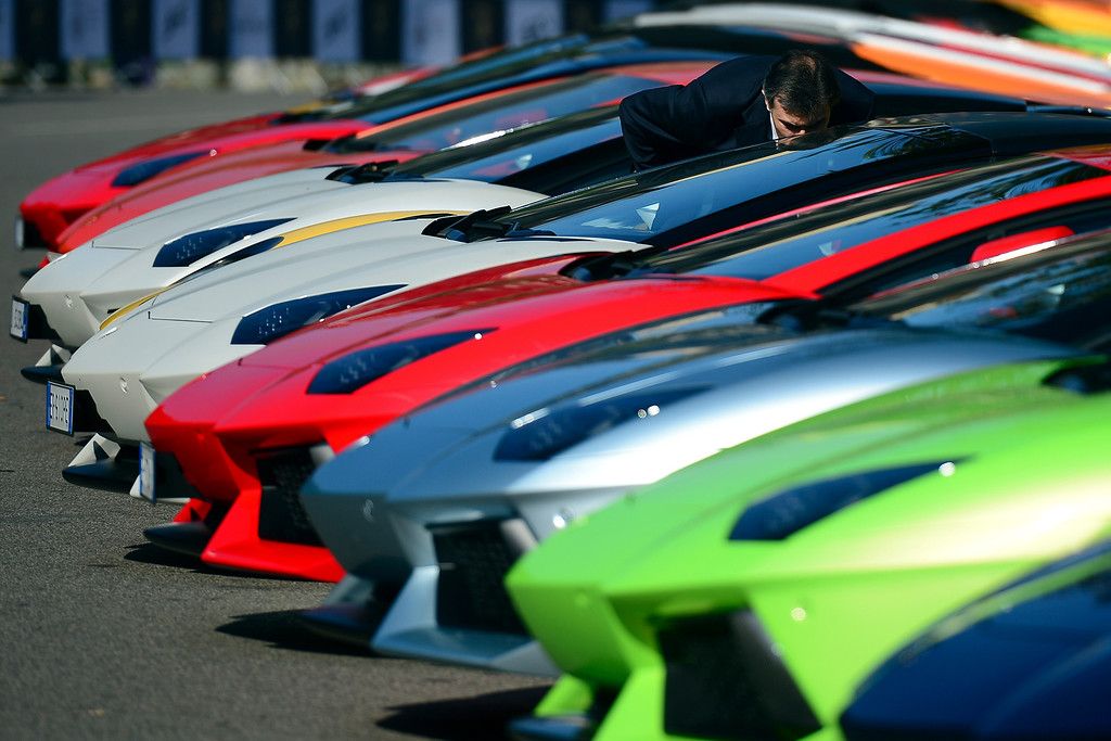 . A man looks at Lamborghini sports are parked on May 7, 2013 in front of Milan\'s Sforza castle in Milan on the eve of the first leg of a 1,200km Grand Tour through Italy to mark the 50th anniversary of the carmaker.   AFP PHOTO / OLIVIER MORIN/AFP/Getty Images
