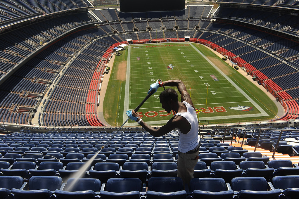 . Q Vorrice power washes stadium seats high up on the 5th level of Sports Authority Field at Mile High  in Denver, CO on Tuesday September 4, 2013. He, and hundreds of other employees,  were preparing the stadium to make it look it\'s best for the NFL season opener with the Denver Broncos taking on the Baltimore Ravens Thursday night.  Photo by Helen H. Richardson/The Denver Post