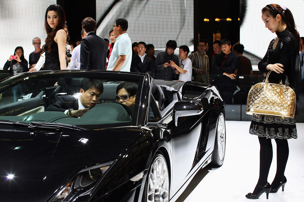 . A sales person (L) introduces a Lamborghini sport car to a Chinese man in the closed section during a special trade visitors opening of the Auto Shanghai 2009 at Shanghai New International Expo Center on April 23, 2009 in Shanghai, China. (Photo by Feng Li/Getty Images)