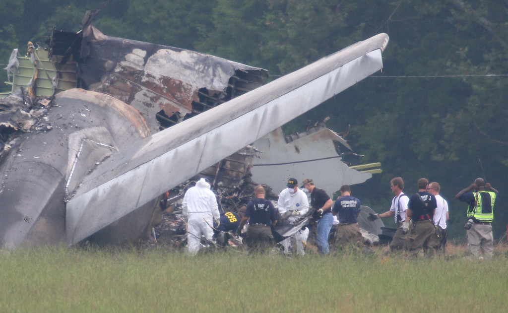 . NTSB investigators remove a large piece of debris from the tail section of the UPS cargo plane that crashed Wednesday on approach to the Birmingham-Shuttlesworth International Airport August 15,  2013 in Birmingham, Ala. Investigators found flight recorders on Thursday that could hold important clues about why the UPS jet crashed at Birmingham\'s airport, killing two pilots. (AP Photo/Hal Yeager)