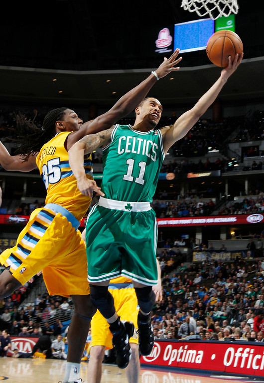 . Boston Celtics guard Courtney Lee, right, drives the lane for a basket past Denver Nuggets forward Kenneth Faried during the first quarter of an NBA basketball game in Denver on Tuesday, Feb. 19, 2013. (AP Photo/David Zalubowski)