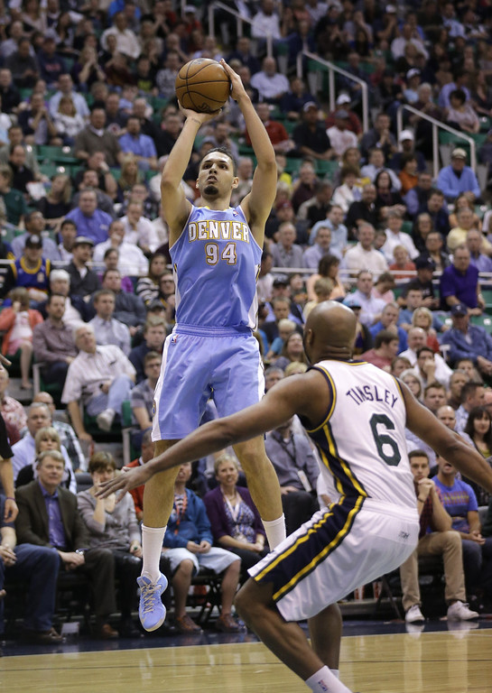 . Denver Nuggets\' Evan Fournier (94) shoots as Utah Jazz\'s Jamaal Tinsley (6) looks on in the second quarter during an NBA basketball game on Wednesday, April 3, 2013, in Salt Lake City. (AP Photo/Rick Bowmer)