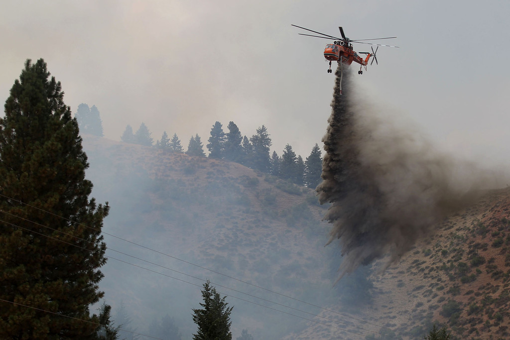 . A helicopter battles the Elk Complex Fire burning near Pine, Idaho, Monday, Aug. 12, 2013.   (AP Photo/Times-News, Ashley Smith)