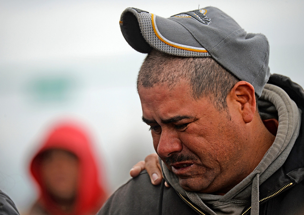 . Sergio Dominguez gathers with other friends and family at the corner of East Colfax Avenue and Dayton Street in Aurora where his son, Juan Carlos Dominguez-Palomino, was killed earlier in a fatal crash, Monday, March 24, 2014.  (Photo by RJ Sangosti/The Denver Post)