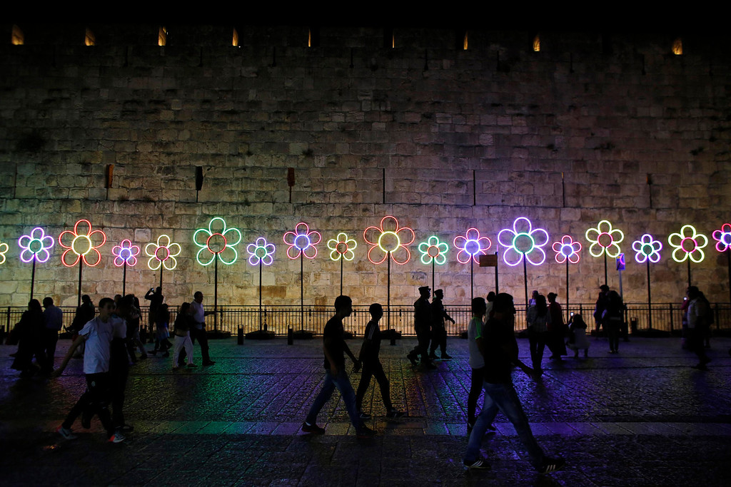 ". People walk past illuminated flowers displayed outside Jerusalem\'s Old City during the ""Jerusalem Light 2013\"" Festival June 5, 2013. The festival opened on Wednesday night and will run for a week in the Old City of Jerusalem, hosting Israeli and international artists who will display their installations throughout the week. REUTERS/Ammar Awad"