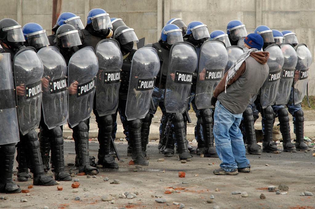 . A protester urinates in front of a row of policemen during riots following the death of a 15-year-old boy in San Carlos de Bariloche June 18, 2010. According to local media, provincial government officials have confirmed that four police officers, involved in the incident which left the boy dead during an alleged robbery, have been removed from their posts. Three people died and at least 12 were injured during the clashes. REUTERS/Alejandra Bartoliche