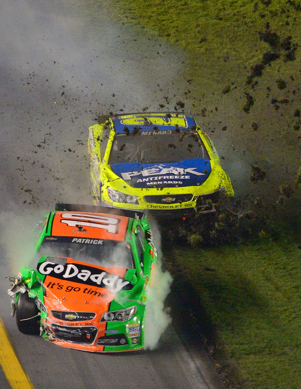 . Danica Patrick (10) and Paul Menard (27) slide in the infield grass after colliding during the NASCAR Daytona 500 auto race at Daytona International Speedway in Daytona Beach, Fla., Sunday, Feb. 23, 2014. (AP Photo/Phelan M. Ebenhack)