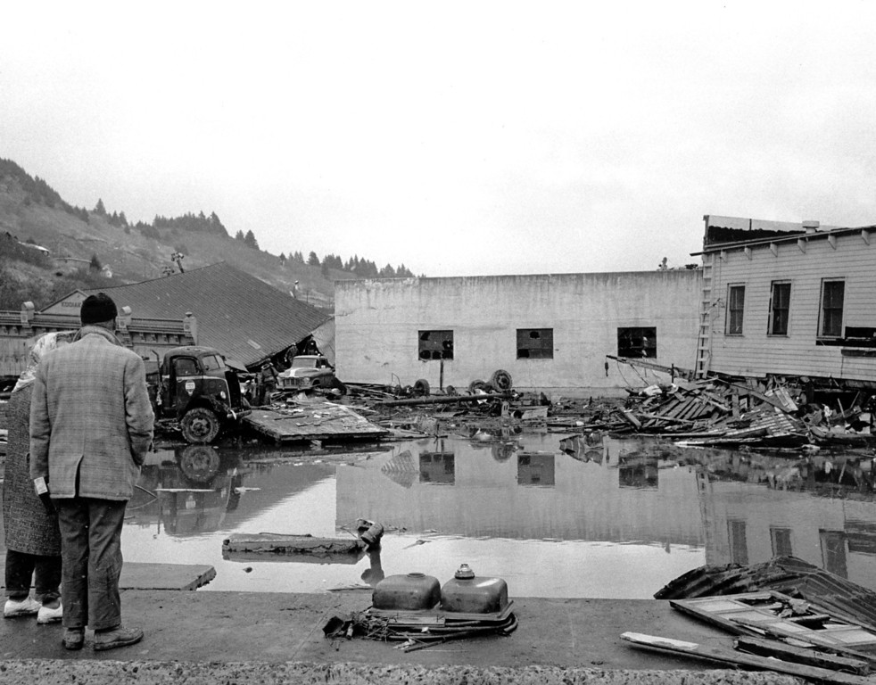 . A forlorn couple stands on a concrete dock viewing the remains of Kodiak, Alaska water front on March 29, 1964.  (AP Photo/stf)