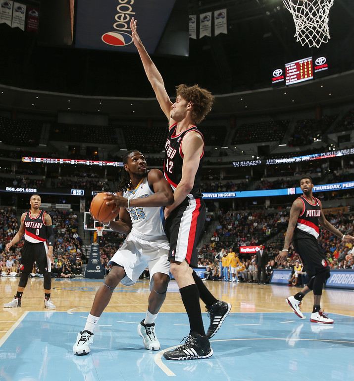 . Denver Nuggets forward Kenneth Faried, left, turns to shoot as Portland Trail Blazers center Robin Lopez covers in the fourth quarter of an NBA basketball game in Denver, Tuesday, Feb. 25, 2014. Portland won 100-95. (AP Photo/David Zalubowski)