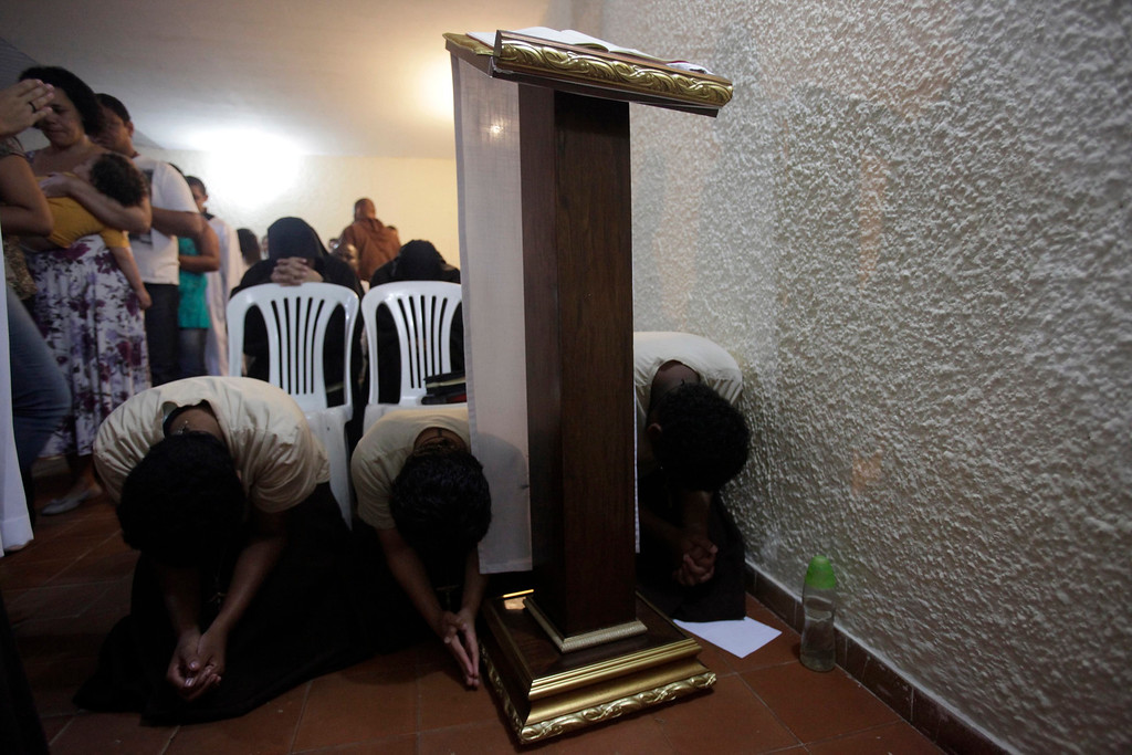 . Members of Franciscan fraternity, O Caminho, (L-R) Dayane Ervencio, Lidiane Pereira, and Juliana Santos, pray during a mass at the group\'s house in the Campo Grande neighbourhood of Rio de Janeiro April 8, 2013. O Caminho (The Way) are a group of Franciscan monks and nuns who help the homeless on the streets of Rio de Janeiro. They consider the election of Pope Francis, the first pontiff to take the name of St Francis of Assisi, to be a confirmation of their beliefs in poverty and simplicity. In July, Pope Francis will visit Rio de Janeiro in his first international trip since assuming the papacy. Picture taken April 8, 2013. REUTERS/Ricardo Moraes