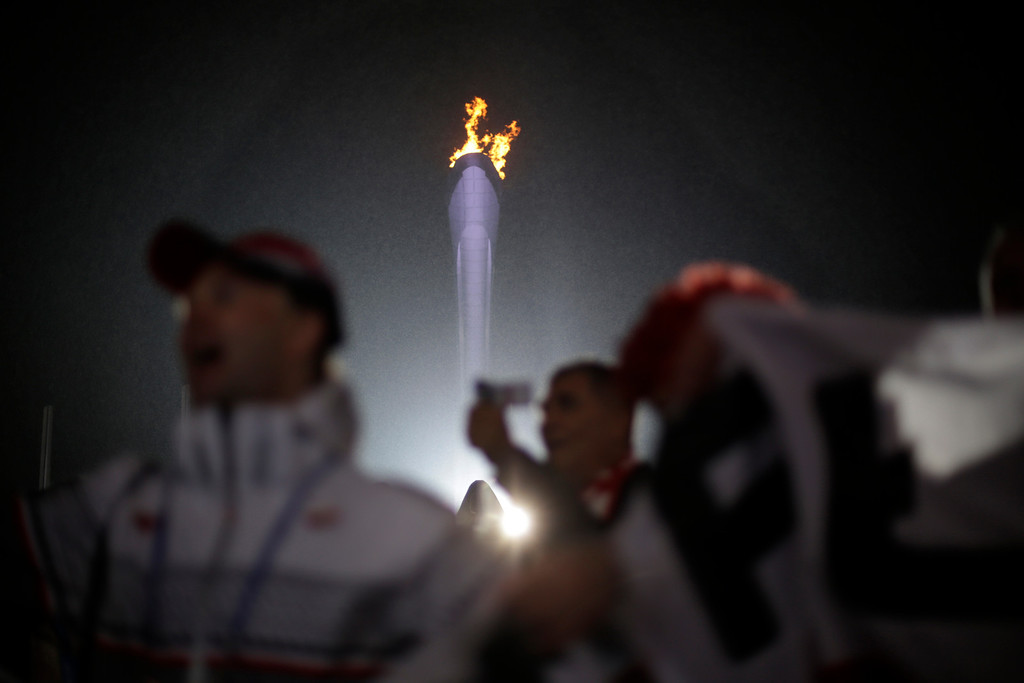 . Fans cheer near the Olympic flame while watching the medals ceremonies at the 2014 Winter Olympics, Sunday, Feb. 16, 2014, in Sochi, Russia. (AP Photo/David Goldman)