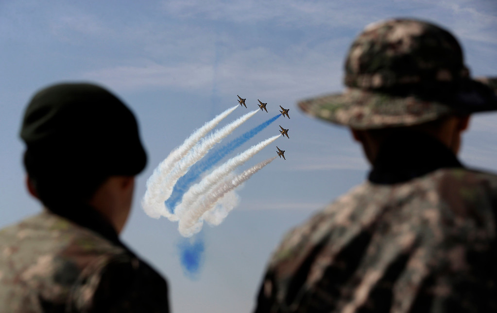 . South Korean soldiers watch the country\'s Air Force\'s aerobatic team, the Black Eagles, perform during the media day for the 65th anniversary of Armed Forces Day at Seoul military airport in Seongnam, South Korea, Friday, Sept. 27, 2013.  (AP Photo/Lee Jin-man)