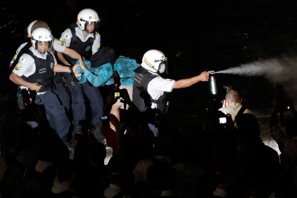 . A military police blast pepper spray at protestors as an unidentified person is detained during an anti-government protest in front of the Brazilian National Congress in Brasilia, Brazil, Thursday, June 20, 2013.  (AP Photo/Eraldo Peres)
