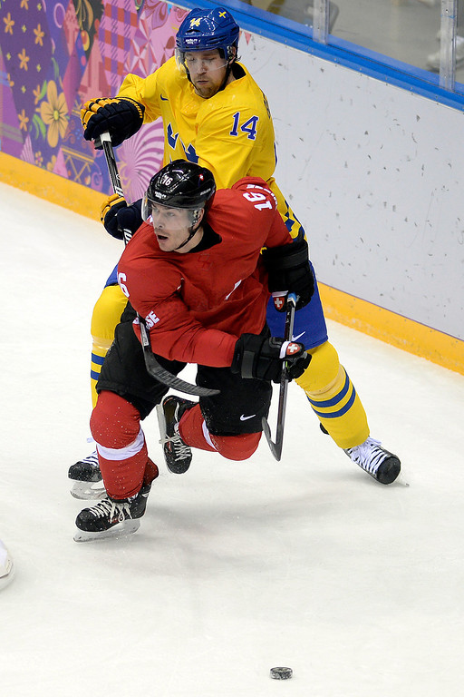 . Switzerland\'s Raphael Diaz skates away from Sweden\'s Patrik Berglund during the action at Bolshoy Arena. Sochi 2014 Winter Olympics on Friday, February 14, 2014. (Photo by AAron Ontiveroz/The Denver Post)