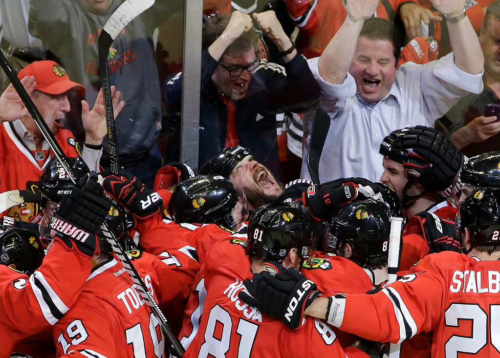. Chicago Blackhawks defenseman Brent Seabrook, center, looking up, celebrates with his teammates after scoring during the overtime in Game 7 of the NHL hockey Stanley Cup Western Conference semifinals against the Detroit Red Wings, Wednesday, May 29, 2013, in Chicago. The Blackhawks won 2-1. (AP Photo/Nam Y. Huh, File)