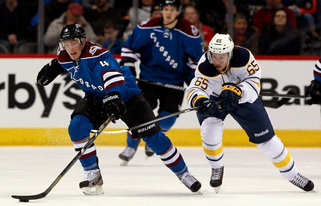 . Colorado Avalanche defenseman Nick Holden, left, reaches out for puck as Buffalo Sabres center Brian Flynn covers in the second period of an NHL hockey game in Denver, Saturday, Feb. 1, 2014. (AP Photo/David Zalubowski)