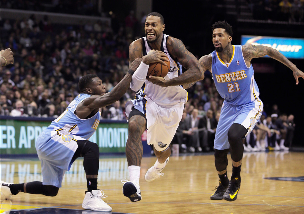 . Memphis Grizzlies\' James Johnson, center, protects the ball from Denver Nuggets\' Nate Robinson, left, and Wilson Chandler (21) during the second half of an NBA basketball game in Memphis, Tenn., Saturday, Dec. 28, 2013. The Grizzlies defeated the Nuggets 120-99. (AP Photo/Danny Johnston)