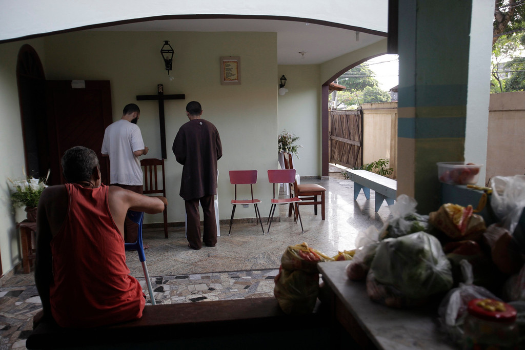 . Alexandre da Silva (L), who is homeless and lives with the brothers of Franciscan fraternity O Caminho, watches as brothers Jose Wellington Damasio and Felipe Lima pray at the fraternity\'s house in the Campo Grande neighborhood of Rio de Janeiro April 2, 2013. O Caminho (The Way), are a group of Franciscan monks and nuns who help the homeless on the streets of Rio de Janeiro. They consider the election of Pope Francis, the first pontiff to take the name of St Francis of Assisi, to be a confirmation of their beliefs in poverty and simplicity. In July, Pope Francis will visit Rio de Janeiro in his first international trip since assuming the papacy. Picture taken April 2, 2013. REUTERS/Ricardo Moraes