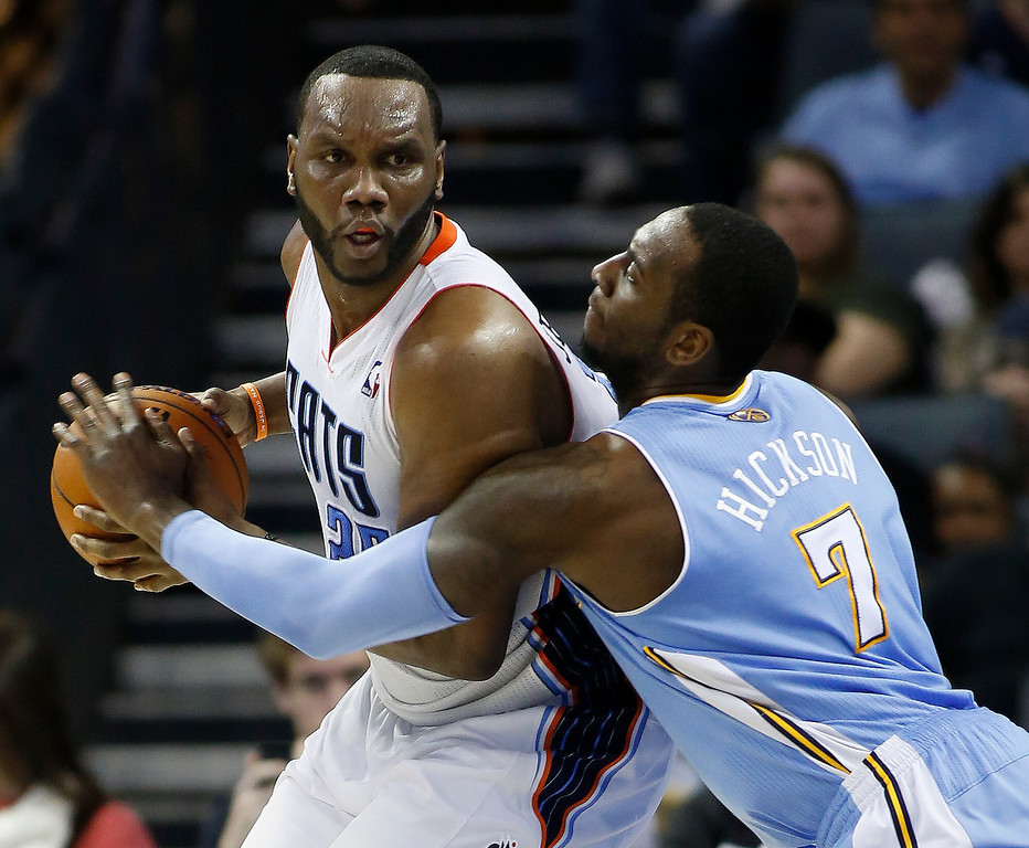. Charlotte Bobcats center Al Jefferson, left, looks to pass against Denver Nuggets center JJ Hickson during the second half of an NBA basketball game in Charlotte, N.C., Monday, March 10, 2014. Charlotte won 105-98. (AP Photo/Nell Redmond)