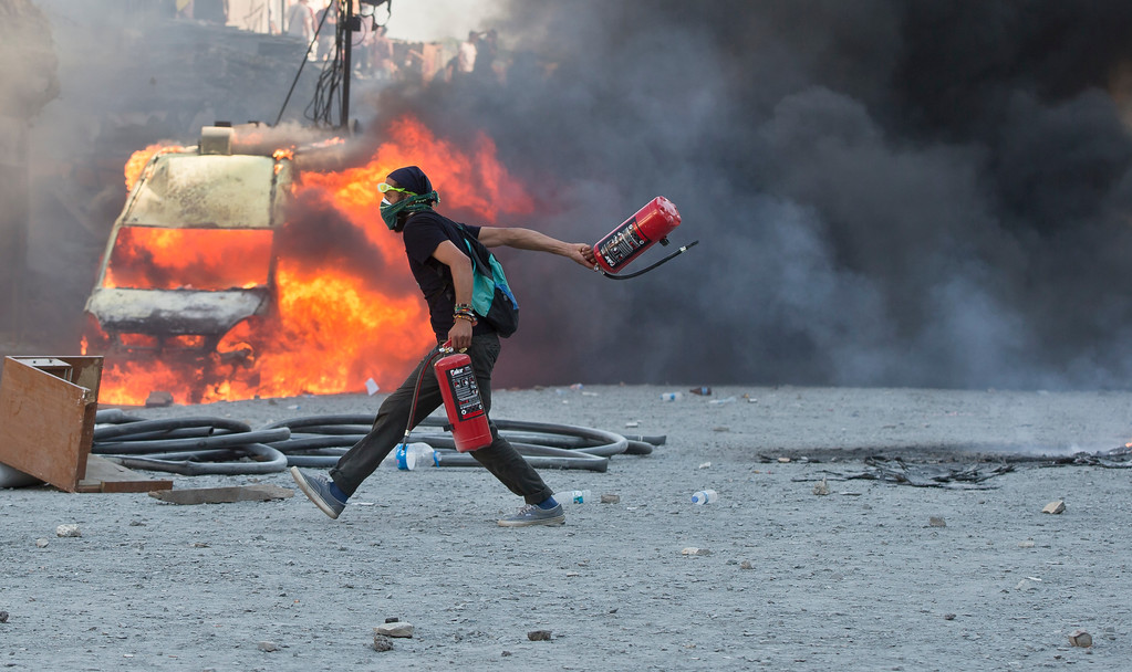 . A man runs carrying fire extinguishers past a burning van during clashes at the Taksim Square in Istanbul Tuesday, June 11, 2013.  (AP Photo/Vadim Ghirda)