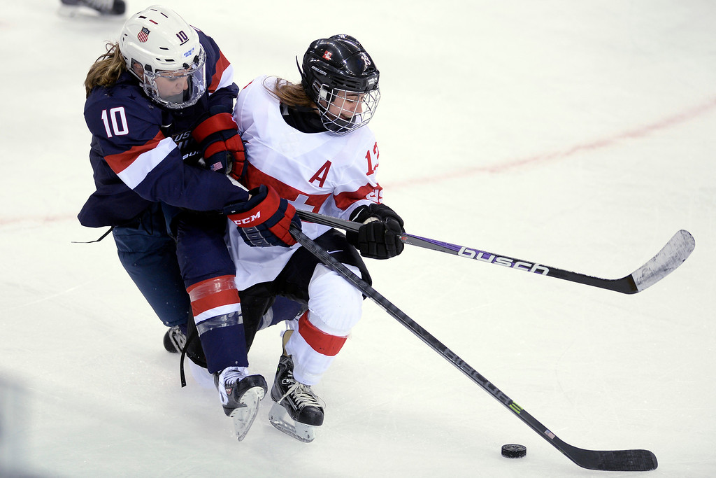 . Sara Benz (13) of the Switzerland and Meghan Duggan (10) of the U.S.A. tangle as they vie of the puck during the third period of the United States\' 9-0 win at the Shayba Arena. Sochi 2014 Winter Olympics on Monday, February 10, 2014. (Photo by AAron Ontiveroz/The Denver Post)