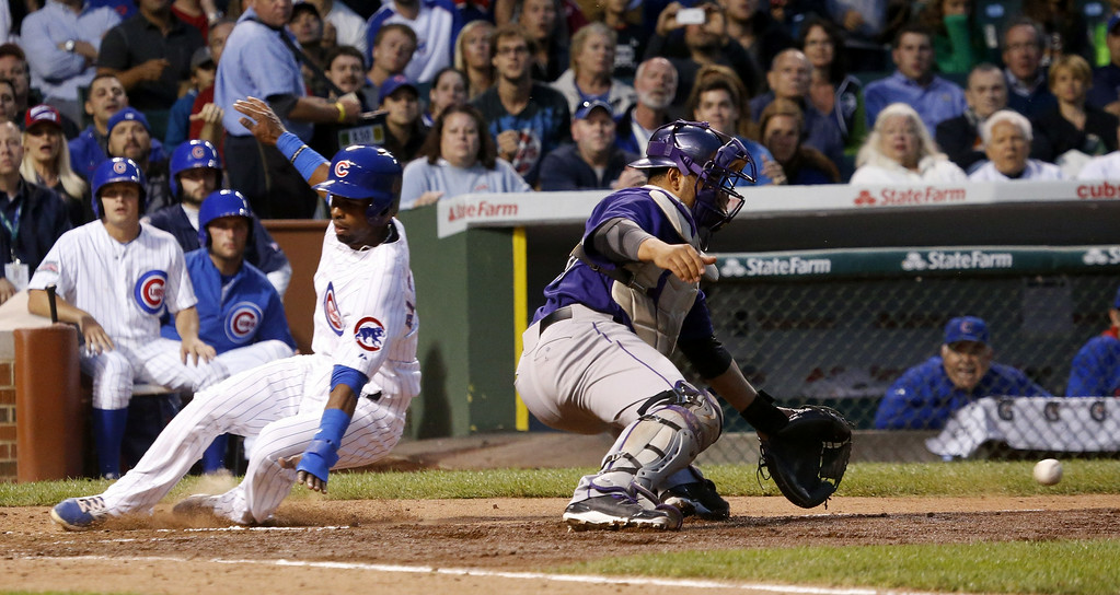 . Chicago Cubs\' Arismendy Alcantara, left, scores past Colorado Rockies catcher Wilin Rosario on a sacrifice fly by Justin Ruggiano and the throw from right fielder Carlos Gonzalez, during the fourth inning of a baseball game Monday, July 28, 2014, in Chicago. (AP Photo/Charles Rex Arbogast)