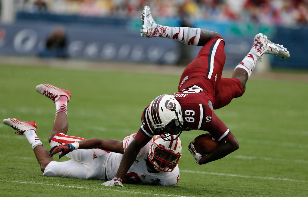 . Jerell Adams #89 of the South Carolina Gamecocks gets tackled by Sojourn Shelton #8 of the Wisconsin Badgers during the first half of the Capital One Bowl on January 1, 2014 in Orlando, Florida.  (Photo by Scott Halleran/Getty Images)