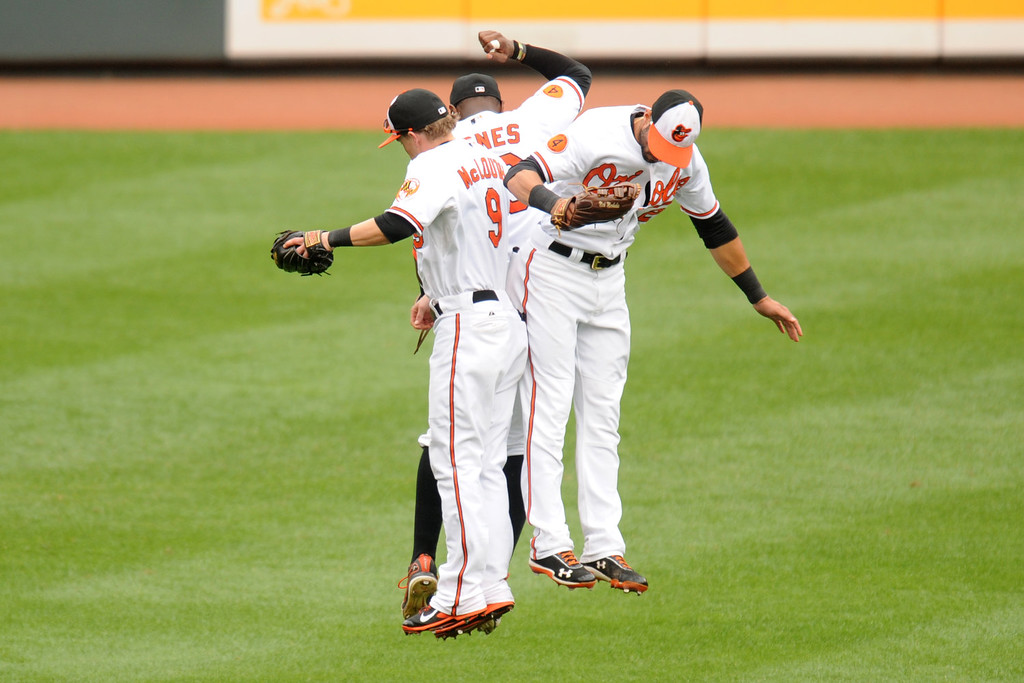 . Nate McLouth #9, Adam Jones #10, and Nick Markakis #21 of the Baltimore Orioles celebrate a win after a baseball game against the Colorado Rockies on August 18, 2013 at Oriole Park at Camden Yards in Baltimore, Maryland.  The Orioles won 7-2.  (Photo by Mitchell Layton/Getty Images)