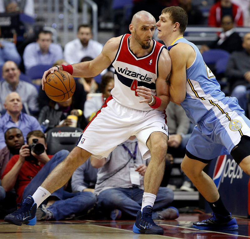 . Washington Wizards center Marcin Gortat (4), from Poland, drives against Denver Nuggets center Timofey Mozgov, right, from Russia, in the first half of an NBA basketball game on Monday, Dec. 9, 2013, in Washington. (AP Photo/Alex Brandon)