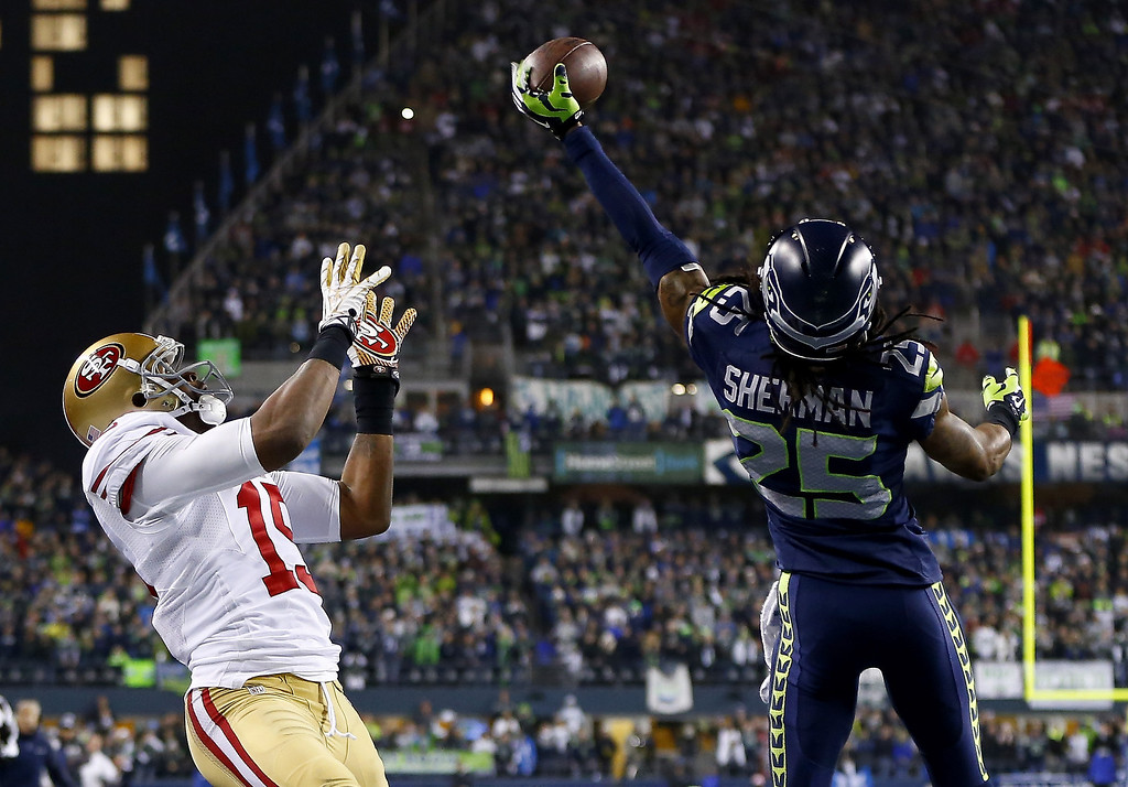 . Cornerback Richard Sherman #25 of the Seattle Seahawks tips the ball up in the air as outside linebacker Malcolm Smith #53 catches it to clinch the victory for the Seahawks against the San Francisco 49ers during the 2014 NFC Championship at CenturyLink Field on January 19, 2014 in Seattle, Washington.  (Photo by Jonathan Ferrey/Getty Images)