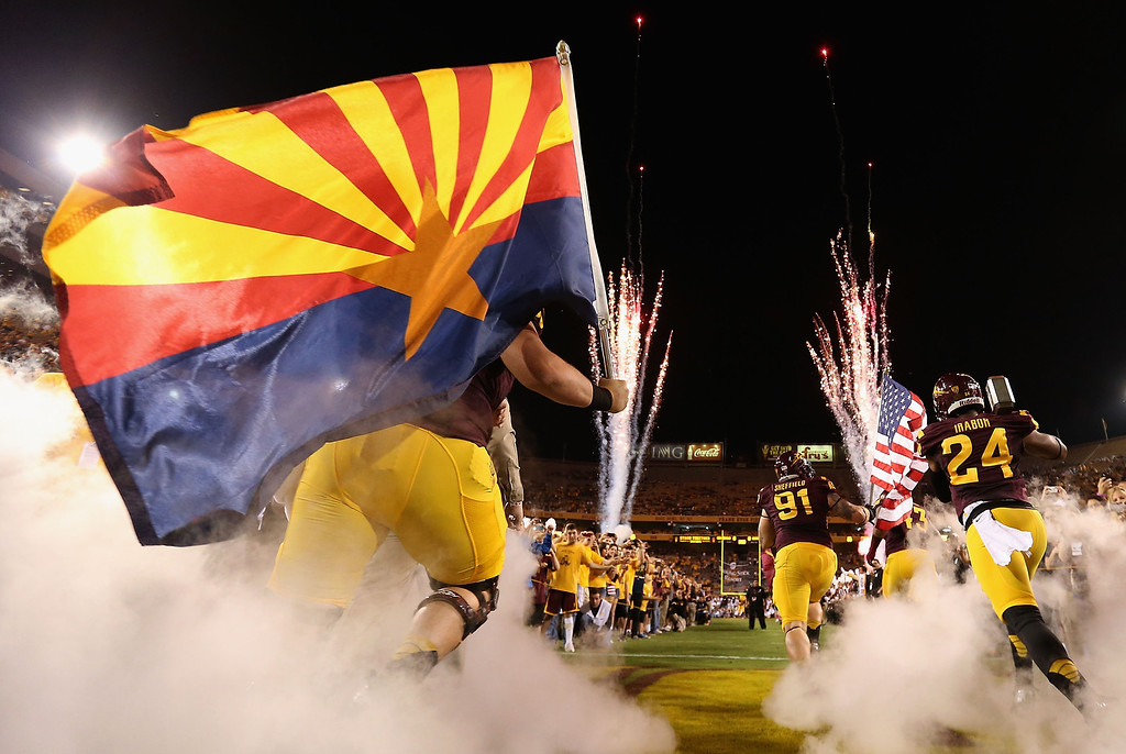 . TEMPE, AZ - OCTOBER 12:  (L-R) Center Kody Koebensky #67, defensive tackle Jake Sheffield #91 and cornerback Osahon Irabor #24 of the Arizona State Sun Devils lead teammates out onto the field before the college football game against the Colorado Buffaloes at Sun Devil Stadium on October 12, 2013 in Tempe, Arizona.  (Photo by Christian Petersen/Getty Images)