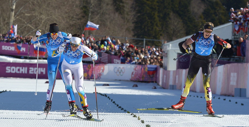. Sweden\'s Charlotte Kalla crosses the finish line to win Gold ahead of Finland\'s Krista Lahteenmaki (L) and Germany\'s Denise Herrmann (R) in the Women\'s Cross-Country Skiing 4x5km Relay at the Laura Cross-Country Ski and Biathlon Center during the Sochi Winter Olympics on February 15, 2014, in Rosa Khutor, near Sochi.      ALBERTO PIZZOLI/AFP/Getty Images