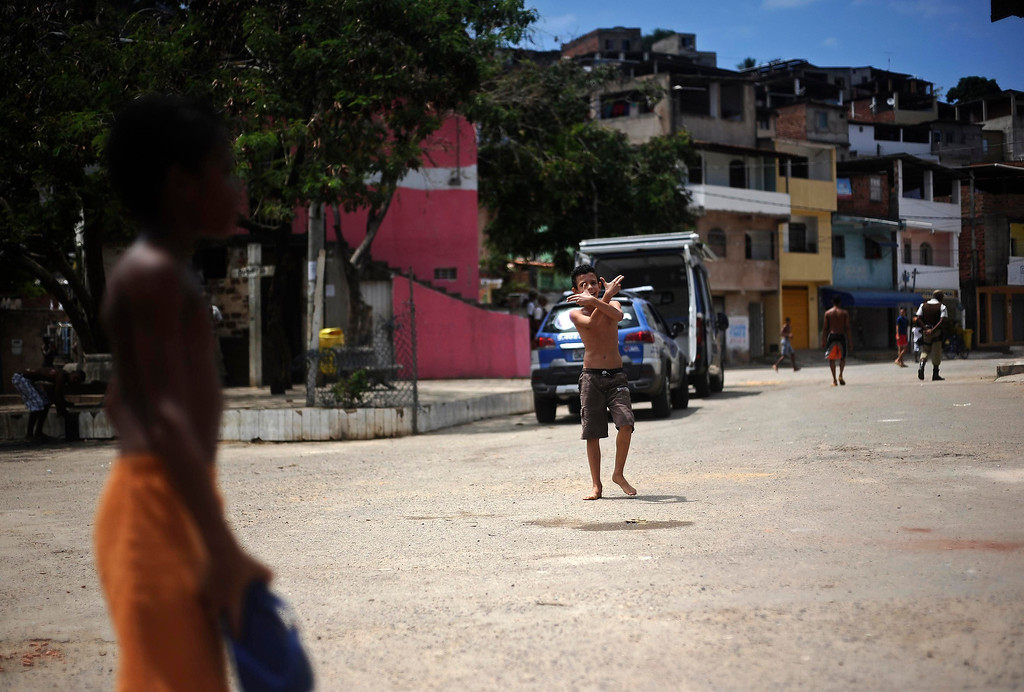 . A boy plays on the street of the Nordeste de Amaralina slum complex as a policeman (back R) patrols in Salvador, Bahia State, March 28, 2013. One of Brazil\'s main tourist destinations and a 2014 World Cup host city, Salvador suffers from an unprecedented wave of violence with an increase of over 250% in the murder rate, according to the Brazilian Center for Latin American Studies (CEBELA). Picture taken March 28, 2013.  REUTERS/Lunae Parracho