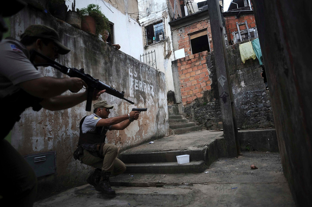. Police react while on patrol in the Nordeste de Amaralina slum complex in Salvador, Bahia State, March 28, 2013. One of Brazil\'s main tourist destinations and a 2014 World Cup host city, Salvador suffers from an unprecedented wave of violence with an increase of over 250% in the murder rate, according to the Brazilian Center for Latin American Studies (CEBELA). Picture taken March 28, 2013.  REUTERS/Lunae Parracho