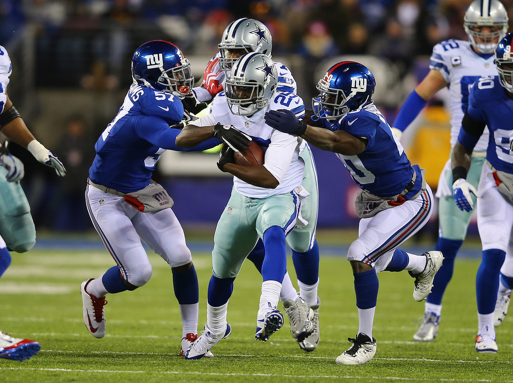 . Lance Dunbar #25 of the Dallas Cowboys is tackled by  Jacquian Williams #57 and  Prince Amukamara #20 of the New York Giants during their game at MetLife Stadium on November 24, 2013 in East Rutherford, New Jersey.  (Photo by Al Bello/Getty Images)