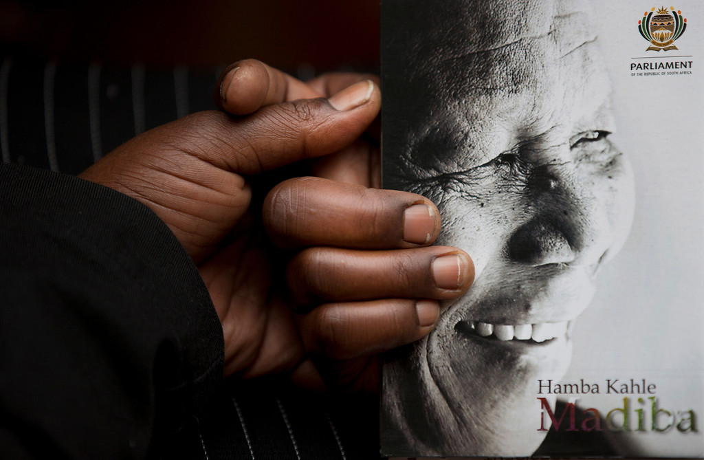 . A man holds the official programme ahead of the memorial service for former South African president Nelson Mandela at the FNB Stadium in Soweto, near Johannesburg, South Africa, Tuesday Dec. 10, 2013. (AP Photo/Peter Dejong)