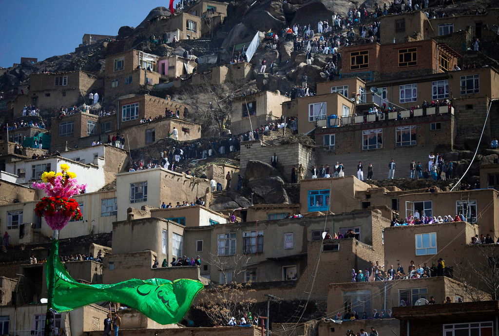 . Hundreds of Afghans line up the hill overlooking the Kart-e Sakhi mosque to see the holy flag in Kabul, Afghanistan, Thursday, March 21, 2013. Afghanistan celebrates Nowruz, marking the first day of spring and the beginning of the year in the Iranian calendar. (AP Photo/Anja Niedringhaus)