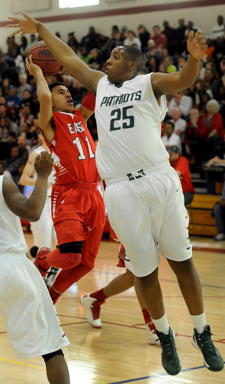 . DENVER, CO. - FEBRUARY 16: Angels guard Brian Carey (11) tried to slip past GW center Cedric Smith (25) in the second quarter. The Denver East High School boy\'s basketball team defeated George Washington 82-20 Saturday afternoon, February 16, 2013.  (Photo By Karl Gehring/The Denver Post)