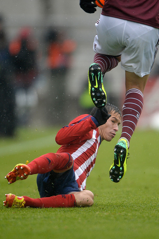 . Eric Avila (15) of Chivas USA slides as Marc Burch (4) of Colorado Rapids jumps over him during the second half. Chivas USA defeated the Colorado Rapids 3-1 on Sunday, May 11, 2014. (Photo by AAron Ontiveroz/The Denver Post)