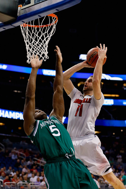 . ORLANDO, FL - MARCH 20:  Luke Hancock #11 of the Louisville Cardinals shoots the ball against Rhamel Brown #5 of the Manhattan Jaspers during the second round of the 2014 NCAA Men\'s Basketball Tournament at Amway Center on March 20, 2014 in Orlando, Florida.  (Photo by Kevin C. Cox/Getty Images)
