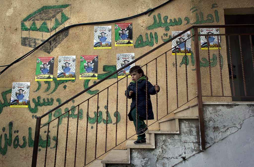 """. A child walks down the stairs of the family home of Ahmed Shehadeh, one of 26 Palestinian prisoners expected to be released later tonight, next to posters with his picture and Arabic that reads \""""welcome,\"""" in the Qalandia refugee camp at the outskirts of the West Bank city of Ramallah, Monday, Dec. 30, 2013. Israel and the Palestinians are gearing up for the expected release by Israel of 26 of the longest-serving Palestinian prisoners, who were all convicted in deadly attacks of Israelis, as part of a U.S.-brokered package to restart peace talks. (AP Photo/Nasser Nasser)"""