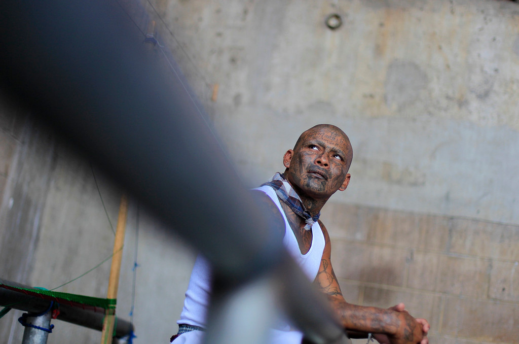 . A jailed gang member sits at the maximum security jail of Izalco in Sonsonate March 5, 2013. Jailed members of the country\'s two most powerful gangs MS-13 and the 18th Street gang (Mara 18), members of civic organizations and Bishop Fabio Colindres celebrated mass to mark the first anniversary since the two gangs signed a truce in March 2012 in an effort to reduce violent crimes in the country. REUTERS/Ulises Rodriguez