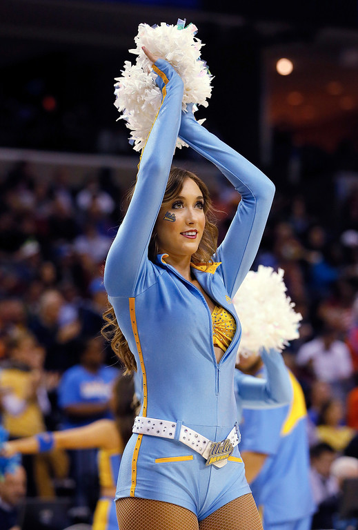 . A UCLA Bruins cheerleader performs during a regional semifinal of the 2014 NCAA Men\'s Basketball Tournament against the Florida Gators at the FedExForum on March 27, 2014 in Memphis, Tennessee.  (Photo by Kevin C. Cox/Getty Images)