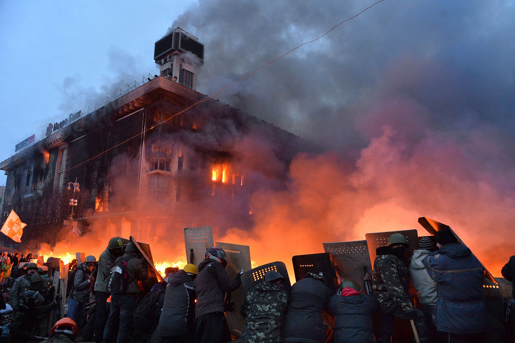 . Anti-government protesters protect themselves behind shields as they clash with the police on Independence Square in Kiev early on February 19, 2014.   AFP PHOTO/SERGEI SUPINSKY/AFP/Getty Images