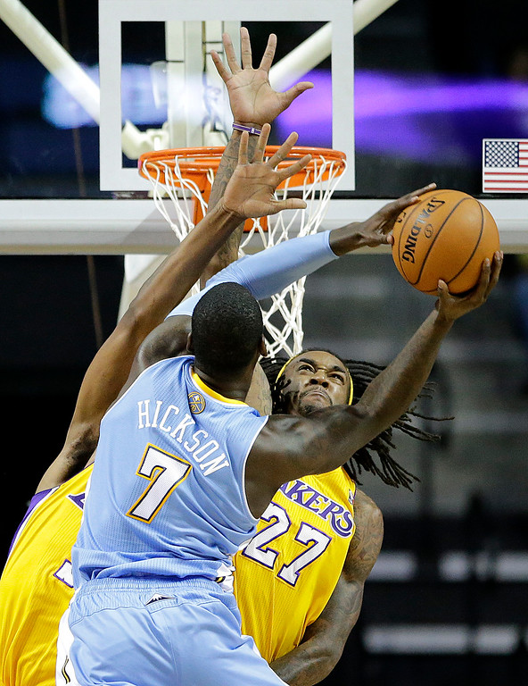 . Denver Nuggets\' J.J. Hickson (7) looks for a shot against Los Angeles Lakers\' Jordan Hill (27) and Shawne Williams in the first half of an NBA preseason basketball game Tuesday, Oct. 8, 2013, in Ontario, Calif. (AP Photo/Jae C. Hong)