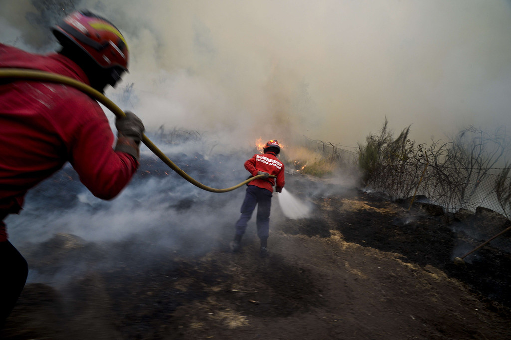 . Firefighters try to extinguish a wildfire in Caramulo, central Portugal on August 29, 2013.   AFP PHOTO / PATRICIA DE MELO  MOREIRA/AFP/Getty Images
